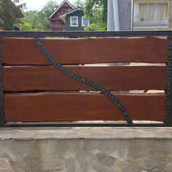 A wrought iron gate - wood - metal, harmony of materials
