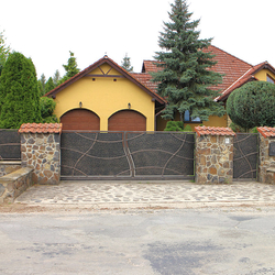 Sliding wrought-iron gate with metal filling; gate and fencing of a family house
